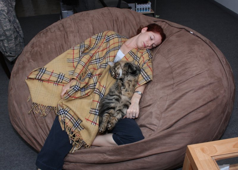 A picture of a woman and her cat snuggling together on a brown, giant Fombag