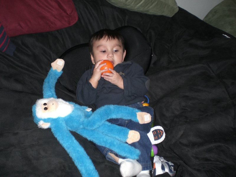 A picture of a young child, and his stuffed monkey, sitting comfortably on a dark brown, giant Fombag