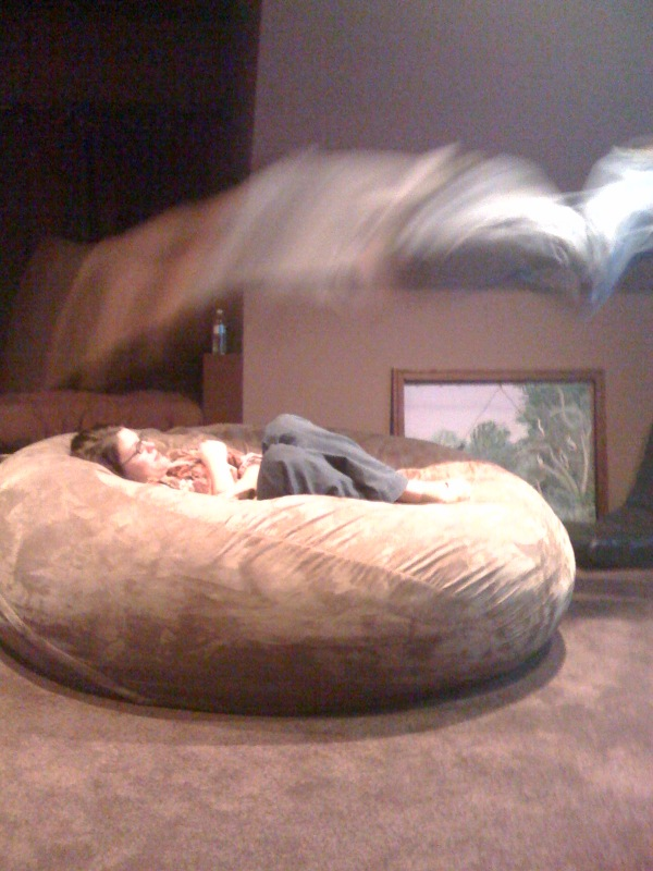 A picture of a husband leaping onto an unsuspecting wife who is curled up in a brown, giant Fombag watching TV