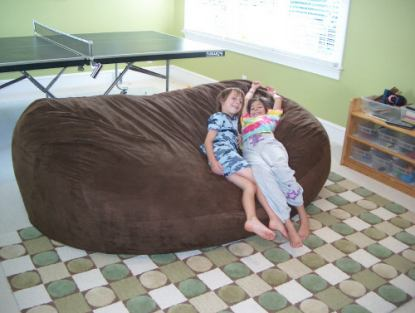 A couple of small children sitting on the side of a giant, brown Fombag