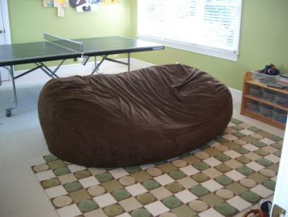 A picture of a giant, brown Fombag in the center of a room with table tennis set up behind it