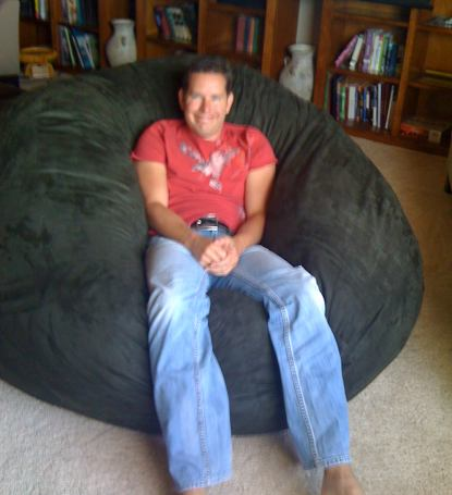 A picture of a middle aged man sitting in the center of a giant, grey Fombag