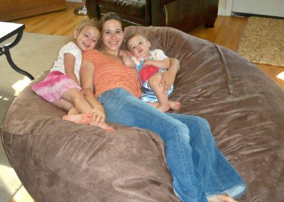 A mother and her two children lying on a giant Fombag
