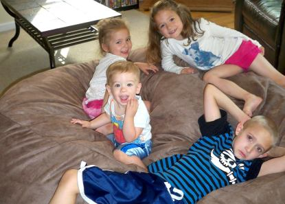 Four young children sitting all across a giant Fombag smiling
