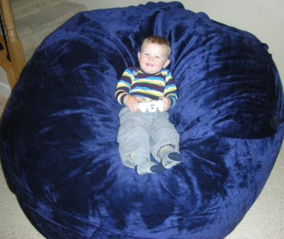 A young child, around the age of 2, sitting in the center of a giant, blue Fombag