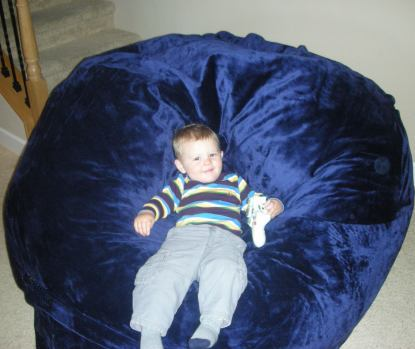 A young child slouching in a giant, blue Fombag while holding an Xbox controller