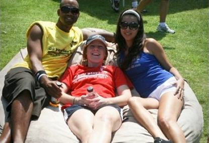 A man and two women all sitting on a 6', tan Fombag outdoors during the VAVI Kickball tournament