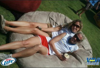 A couple of woman lounging in the center of a 6', tan Fombag during the VAVI kickball tournament