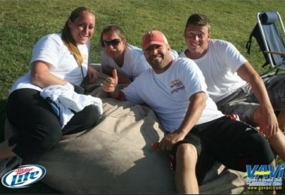 A group of four people, two men and two women, all relaxing on the 6', tan Fombag during the VAVI kickball tournament
