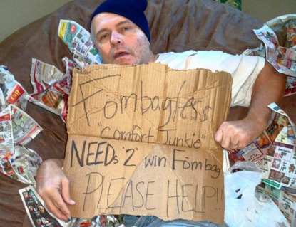 A picture of a man pretending to be a 'comfort junkie' holding up a sign as he lays on a brown, giant Fombag