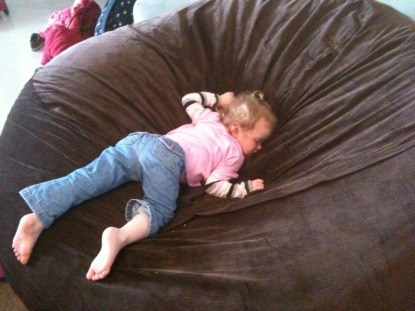 A picture of a small child sleeping, face down, in a giant, brown Fombag